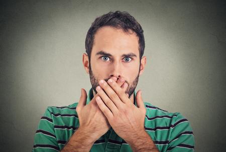 Close-up portret man met de hand over zijn mond, sprakeloos, geïsoleerd op grijze muur achtergrond