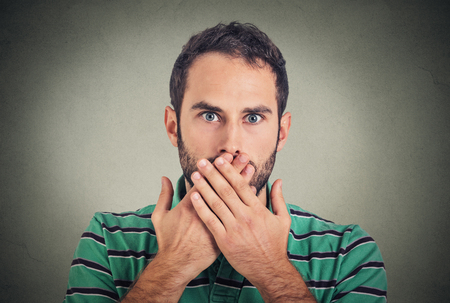 Closeup portrait man with hand over his mouth, speechless, isolated on gray wall background Stock Photo