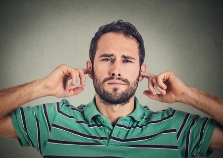 oido: tiro en la cabeza el hombre disgustado que tapa los o�dos con los dedos no quiere escuchar aislados sobre fondo gris de la pared Foto de archivo