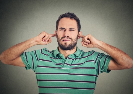 avoid: headshot displeased man plugging ears with fingers doesnt want to listen isolated on gray wall background