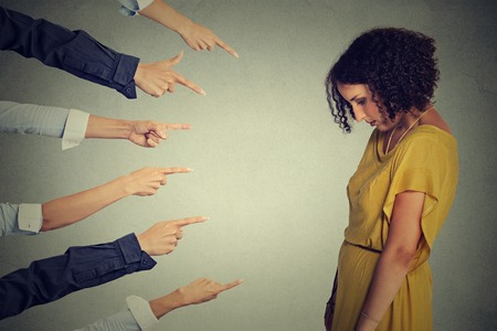 societies: Concept accusation guilty person girl. Side profile sad upset woman looking down many fingers pointing at her back isolated grey office wall background. Negative human face expression emotion feeling Stock Photo