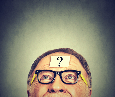 unknown age: thinking man with question mark on gray wall background Stock Photo