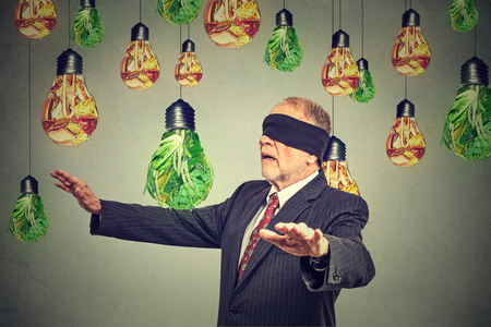 food industry: Blindfolded senior man walking through light bulbs shaped as junk food and green vegetables isolated on gray wall background. Diet choice right nutrition healthy lifestyle concept Stock Photo