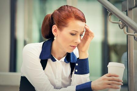 Retrato subrayó mujer joven triste con la taza de café que se sienta al aire libre. Ciudad estrés estilo de vida urbano Foto de archivo