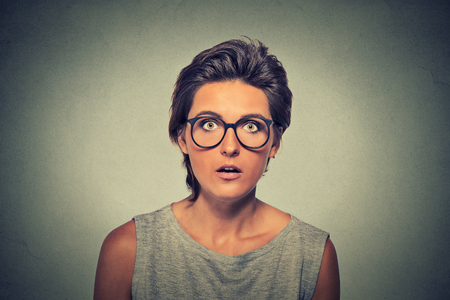 asustado: Retrato de mujer joven con expresi�n de la cara de miedo asombrado aislada sobre fondo gris de la pared