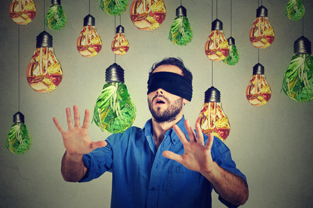 light diet: Blindfolded young man walking through light bulbs shaped as junk food and green vegetables isolated on gray wall background. Diet choice right nutrition healthy lifestyle concept Stock Photo