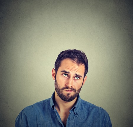 Portrait closeup funny confused skeptical man thinking looking up isolated on gray wall background with copy space above head. Human face expressions, emotions, feelings, body language Stockfoto