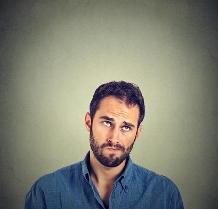 Retrato de cerca confundido divertida hombre de pensamiento escéptico mirando hacia arriba aislados en el fondo gris de la pared con copia espacio por encima de la cabeza. expresiones faciales humanas, las emociones, los sentimientos, el lenguaje corporal