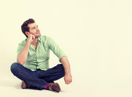 relajado: joven feliz del retrato en camisa verde y pantalones vaqueros sentados en el suelo. Individuo sonriente relajado mirando para arriba y sueño en su futuro aislado en blanco la pared de fondo amarillo con el espacio blanco de la copia