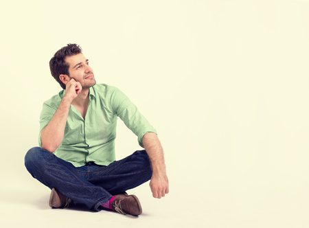 wall background: Portrait happy young man in green shirt and blue jeans sitting on the floor. Smiling relaxed guy looking up and dreaming at his future isolated on white yellow wall background with blank copy space