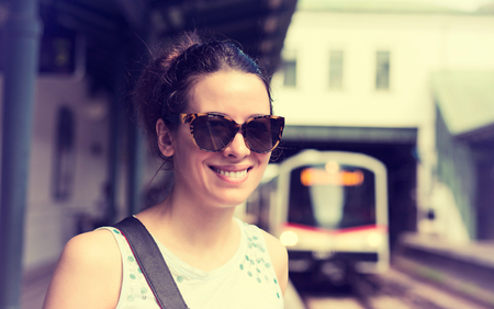 subway platform: Closeup portrait young woman standing on subway platform waiting approaching train