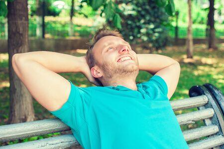 relajado: Primer retrato de un hombre feliz hermoso joven en camisa mirando hacia arriba en el pensamiento, relajante en un banco aislado en el fondo del parque