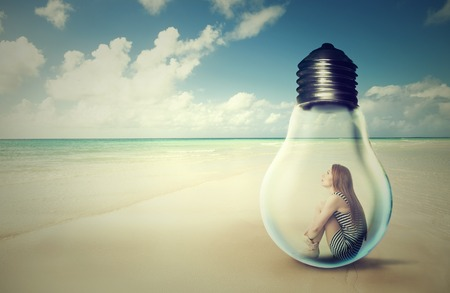 introvert: young woman sitting inside a light bulb on a beach looking at the ocean view. Loneliness outlier person. After storm survivor message to future generation concept