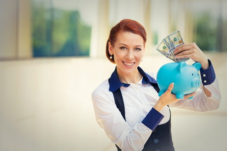 depositing: Closeup portrait super happy excited successful young business woman depositing money dollars in piggy bank isolated outdoors background. Positive emotion face expression feeling. Financial reward