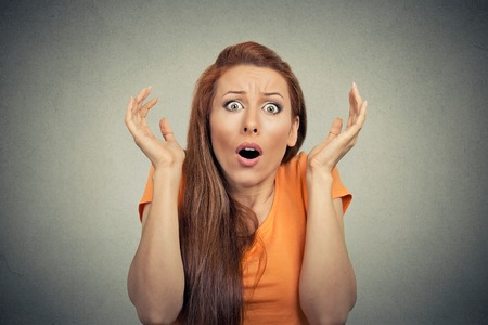 woman looking: Portrait frightened shocked scared woman looking at camera isolated on gray wall background. Human emotion facial expression body language unexpected reaction