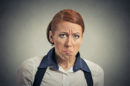 bitchy: Closeup portrait young serious angry grumpy woman isolated on gray wall background. Negative human emotion feelings face expression reaction