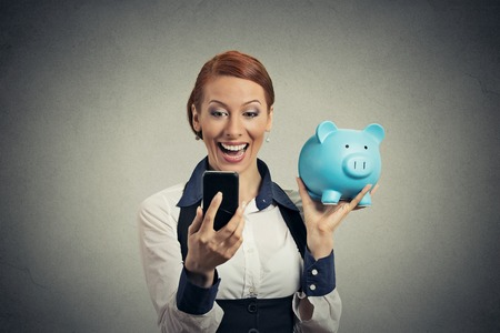 saving: Laughing happy young woman holding piggy bank looking at smart phone isolated on gray background. Financial savings banking concept, customer satisfaction contract agreement. Positive face expression Stock Photo