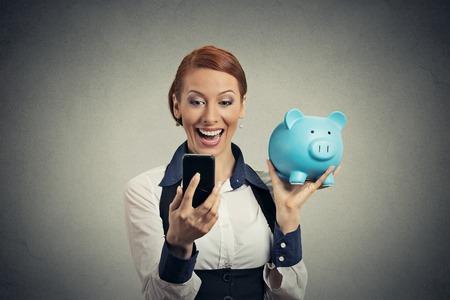 Ridere giovane donna felice azienda salvadanaio guardando smart phone isolato su sfondo grigio. Risparmio finanziario concetto bancario, la soddisfazione del cliente accordo contrattuale. Espressione del viso positivo