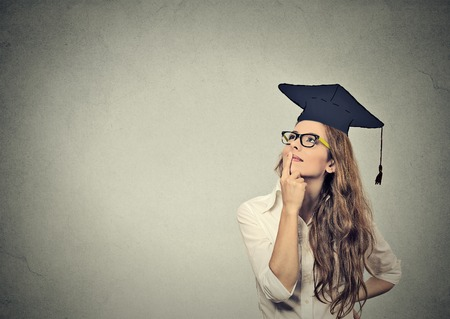 successful student: Portrait closeup beautiful thoughtful graduate graduated student girl young woman in cap gown looking up thinking isolated gray wall background. Graduation ceremony future career concept