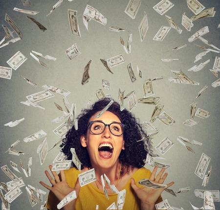 mujer feliz del retrato en vidrios exults bombeo puños celebra éxtasis éxito bajo una lluvia de dinero cayendo billetes de dólares billetes aislados sobre fondo gris de la pared con el espacio de la copia