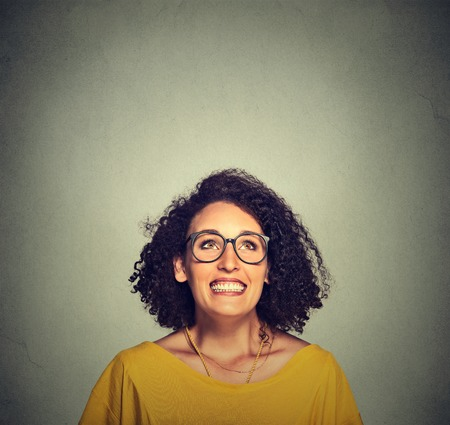 exaggerate: Portrait of a super excited happy funky girl in glasses looking up isolated on grey wall background Stock Photo