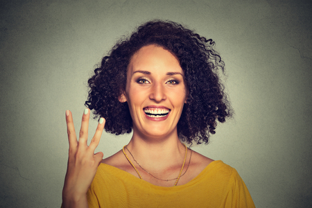 three fingers: Closeup portrait of young pretty woman giving a three fingers sign gesture with hand isolated on gray wall background. Positive human emotions, facial expressions, feeling, symbols, body language