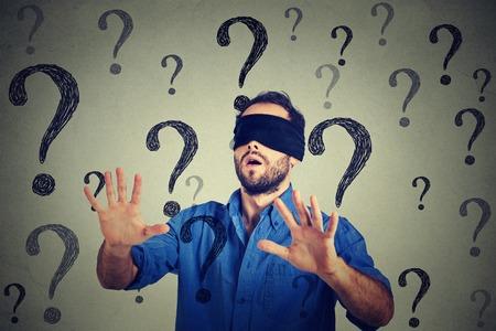 ojos vendados: Retrato del hombre de negocios con los ojos vendados estirando los brazos hacia fuera que camina a trav�s de muchas preguntas aisladas en el fondo de la pared gris
