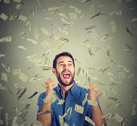 loteria: Hombre feliz Retrato regocija puños de bombeo extática celebra el éxito gritando bajo la lluvia de dinero cayendo cuentas de dólar billetes aislados fondo gris, con copia espacio. Concepto de la libertad financiera