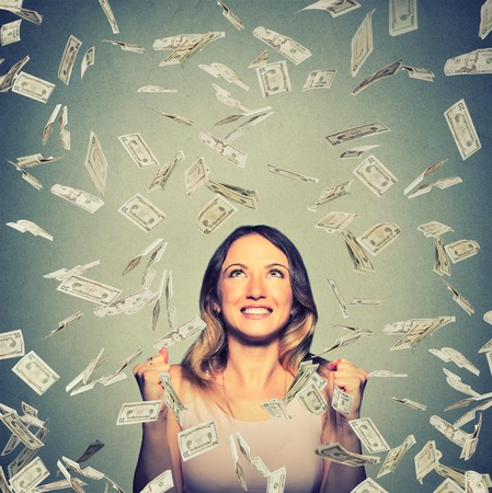 capital: Portrait happy woman exults pumping fists ecstatic celebrates success under a money rain falling down dollar bills banknotes isolated on gray wall background with copy space