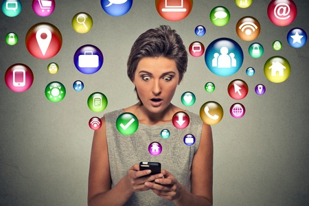 media: communication technology mobile high tech concept. Closeup surprised young woman using texting on smartphone with social media application symbols icons flying out of screen isolated grey background