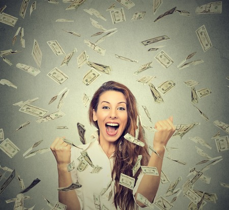 dividend: Portrait happy woman exults pumping fists ecstatic celebrates success under a money rain falling down dollar bills banknotes isolated on gray wall background with copy space