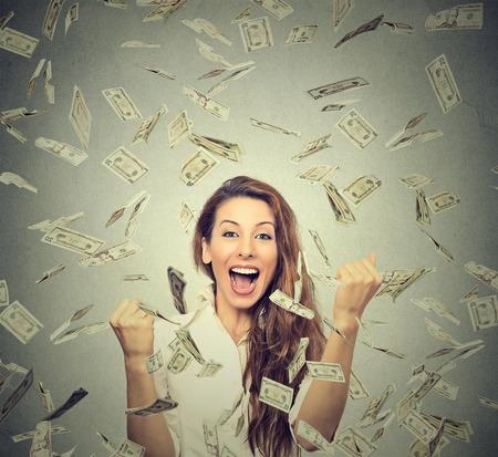 cash: Retrato mujer feliz se regocija puños de bombeo extática celebra éxito bajo una lluvia de dinero cayendo billetes de dólar billetes aislados sobre fondo gris de la pared con el espacio de la copia