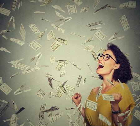 dinero: mujer feliz del retrato en vidrios exults bombeo puños celebra éxtasis éxito bajo una lluvia de dinero cayendo billetes de dólares billetes aislados sobre fondo gris de la pared con el espacio de la copia