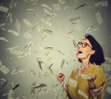 reward: Portrait happy woman in glasses exults pumping fists ecstatic celebrates success under a money rain falling down dollar bills banknotes isolated on gray wall background with copy space