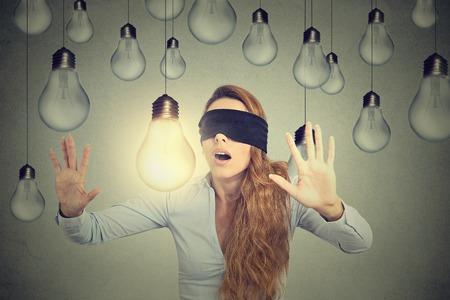 Mujer joven con los ojos vendados caminando por bombillas en busca de brillante idea Foto de archivo