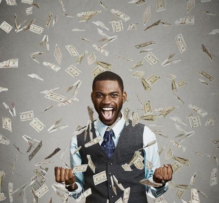 efectivo: Hombre feliz Retrato regocija puños de bombeo extática celebra el éxito gritando bajo la lluvia de dinero cayendo cuentas de dólar billetes aislados fondo gris, con copia espacio. Concepto de la libertad financiera