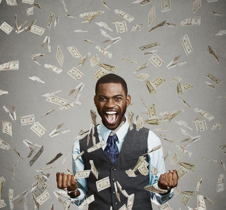 reward: Portrait happy man exults pumping fists ecstatic celebrates success screaming under money rain falling down dollar bills banknotes isolated gray background with copy space. Financial freedom concept