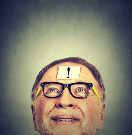 alert: Closeup portrait of old thinking man with glasses and exclamation sign mark on forehead looking up isolated on gray wall background with copy space. Positive face expression