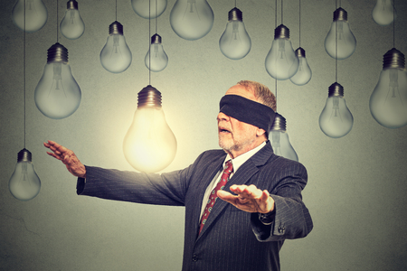 people human mind: Blindfolded senior elderly man walking through light bulbs searching for bright idea