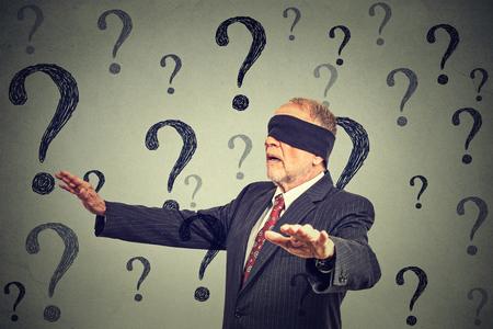 Portrait homme d'affaires les yeux bandés, étirant ses bras en marchant à travers de nombreuses questions isolées sur fond de mur gris Banque d'images