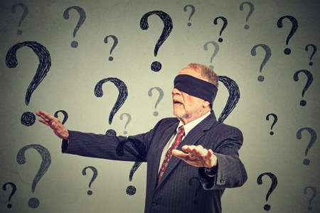 Portrait business man blindfolded stretching his arms out walking through many questions isolated on gray wall background