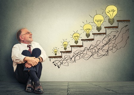Excited happy elderly executive man relaxed sitting on a floor in his office looking up at business success company growth graph made of light bulbs isolated on gray wall texture background