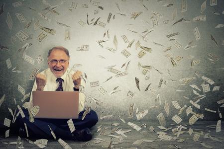 hombre de negocios de alto con un ordenador portátil construcción de negocio en línea que hace cuentas de dinero en efectivo en dólares que caen hacia abajo. lluvia de dinero. empresario de TI de trabajo en línea concepto de economía éxito Foto de archivo