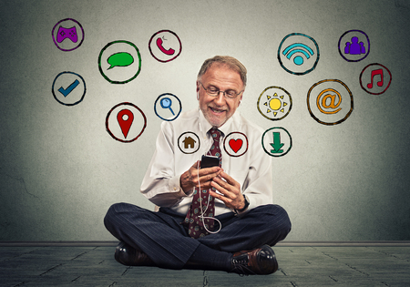 cloud search: Happy senior man sitting on floor using texting on smartphone browsing web social media application icons flying out of cellphone isolated grey background. 4g data plan. Communication tech concept Stock Photo