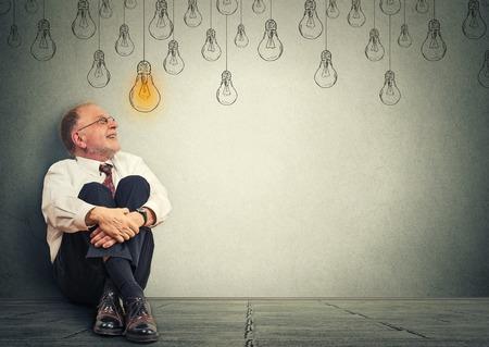 Retrato pensando anciano en gafas sentado en un piso mirando hacia arriba con bombilla idea sobre la cabeza aislada sobre fondo de pared gris