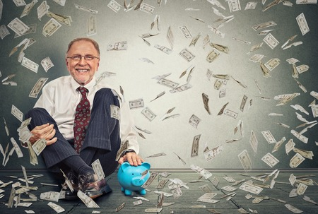 economy: Excited happy senior man sitting on a floor with piggy bank under a money rain isolated on gray wall background. Positive emotions financial success luck good economy concept
