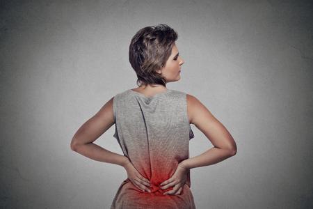 mujer joven con dolor de espalda dolor de espalda baja coloreado en rojo aislado en fondo gris Foto de archivo