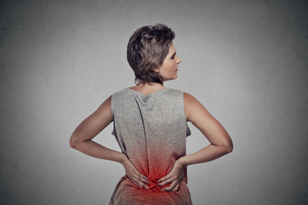 BACK bone: young woman with backache lower back pain colored in red isolated on gray background Stock Photo