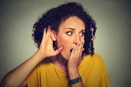 secretly: Closeup portrait surprised young nosy woman hand to ear gesture carefully intently secretly listening juicy gossip conversation news privacy violation isolated grey background. Human face expression