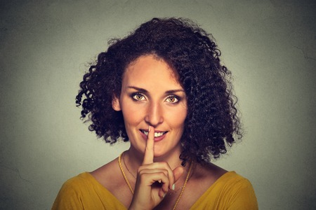 noiseless: Closeup portrait happy young woman placing finger on lips asking shhhhh, quiet, silence isolated on gray wall background. Human face expressions, signs, emotions, feelings, body language reaction Stock Photo